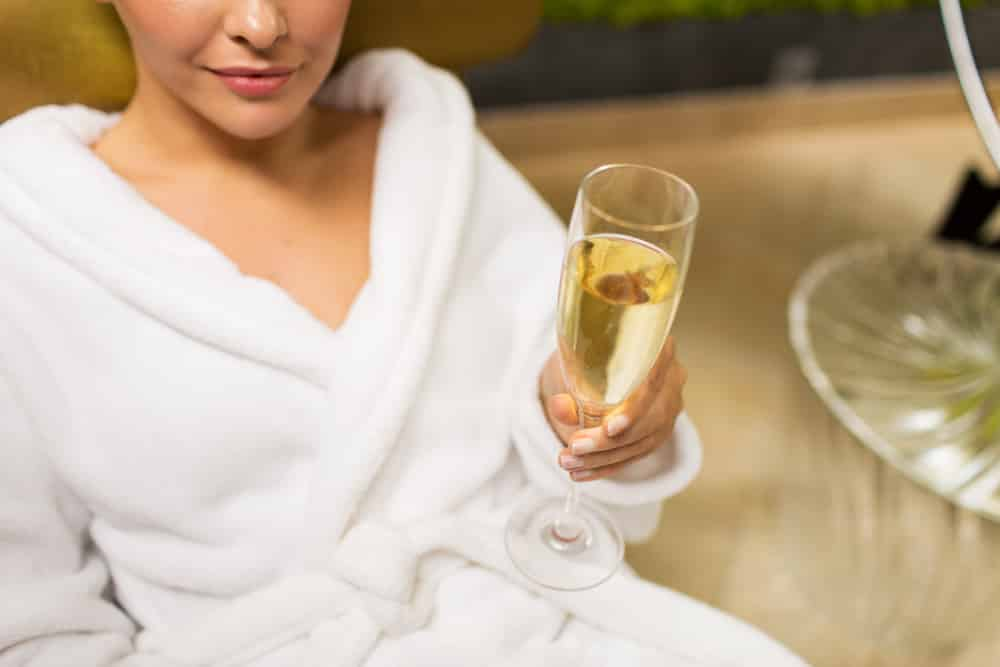 person-in-robe-holding-champagne-glass