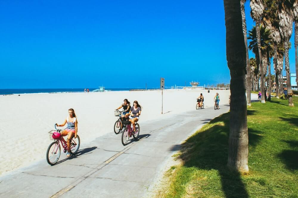 people-biking-along-water